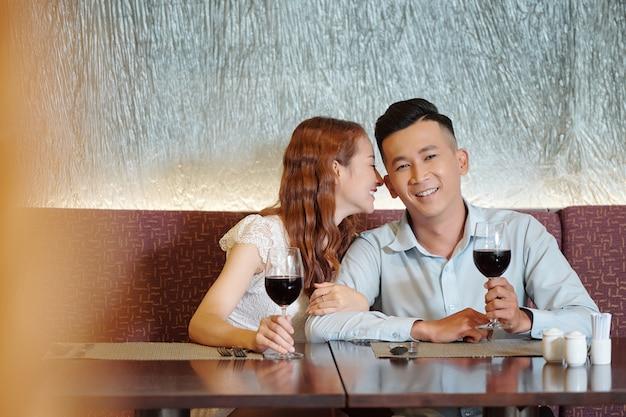 Glimlachende vrouw die woorden van liefde fluistert in het oor van haar vriend wanneer ze aan de tafel van het restaurant zitten