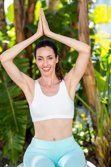 Glimlachende vrouw die yoga op een zonnige dag doet