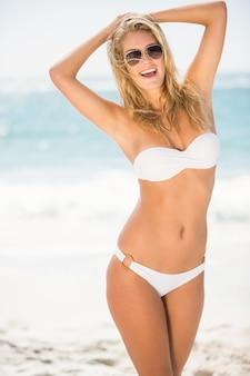 Glimlachende vrouw die zich bij het strand bevindt