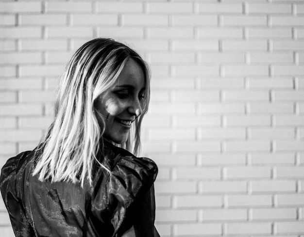 Glimlachende vrouw die zich dichtbij bakstenen muur bevindt