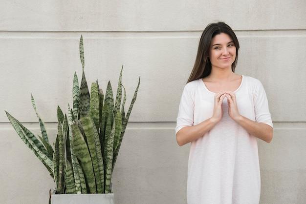 Glimlachende vrouw die zich dichtbij groene houseplant bevindt