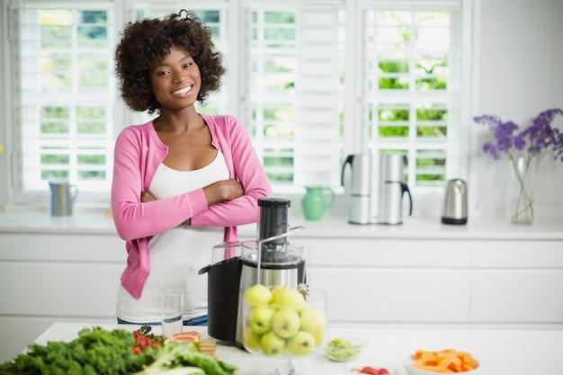 Glimlachende vrouw die zich met die wapens bevinden in keuken worden gekruist