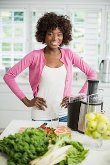 Glimlachende vrouw die zich met hand op heup in keuken bevindt