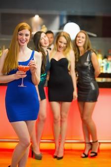 Glimlachende vrouw die zich voor haar vrienden bevindt die cocktail houden