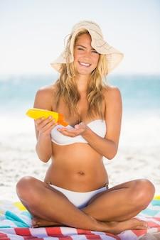 Glimlachende vrouw die zonnescherm toepast