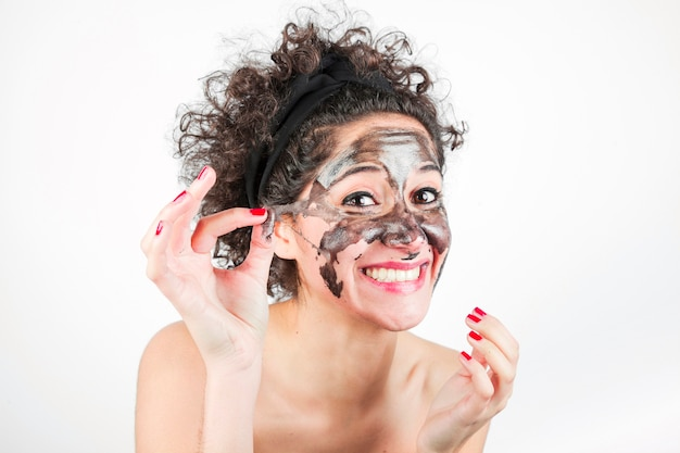 Glimlachende vrouw die zuiverend masker verwijdert uit haar gezicht over witte achtergrond