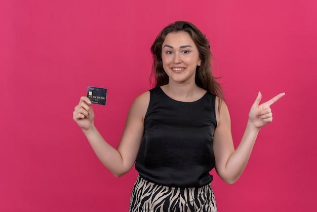 Glimlachende vrouw die zwart onderhemd draagt dat een bankkaart houdt en naar kant wijst - op roze muur