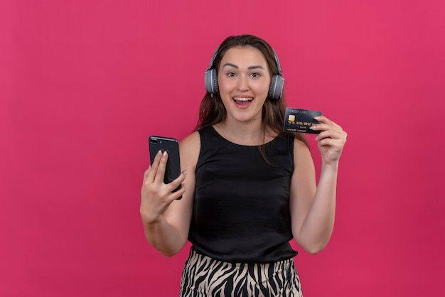 Glimlachende vrouw die zwart onderhemd draagt dat hoofdtelefoons draagt die telefoon en bankkaart op roze muur houden