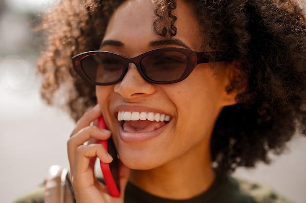 Glimlachende vrouw. een close-up foto van een lachende schattige vrouw die aan de telefoon praat
