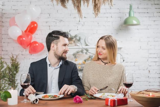 Glimlachende vrouw en man die van diner genieten