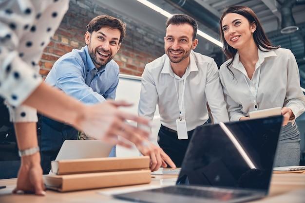 Glimlachende vrouw en twee blanke knappe mannen bespreken project met laptop en map papier