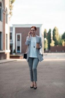 Glimlachende vrouw. full-length portret van een stijlvolle jonge zakenvrouw met een papieren kopje koffie glimlachend tijdens het praten aan de telefoon