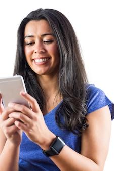 Glimlachende vrouw gebruikend een smartphoen en dragend een smartwatch