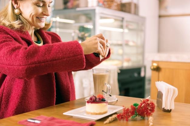 Glimlachende vrouw. glimlachende rijpe modieuze vrouw met gezichtsrimpels die suiker in haar koffie zetten
