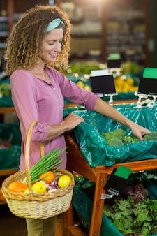 Glimlachende vrouw het kopen groenten in organische sectie