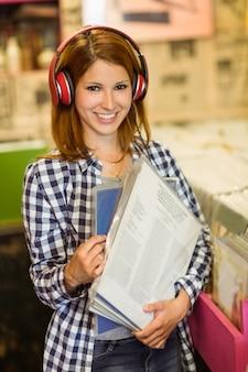 Glimlachende vrouw het luisteren muziek en het houden van vinyls