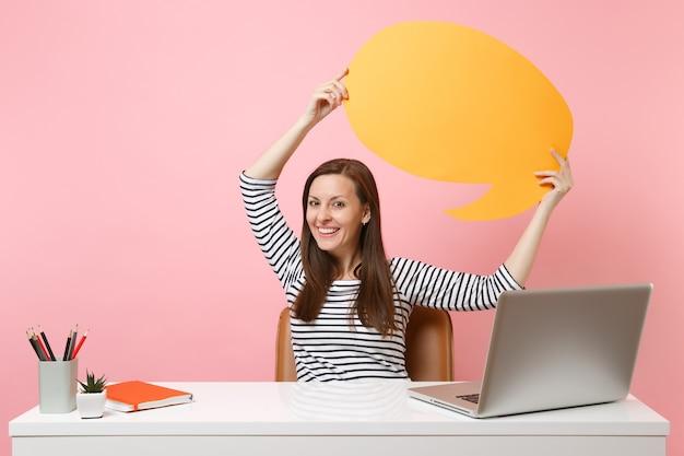 Glimlachende vrouw houdt gele lege blanco vast. zeg cloud-spraakballonwerk aan een wit bureau met pc-laptop