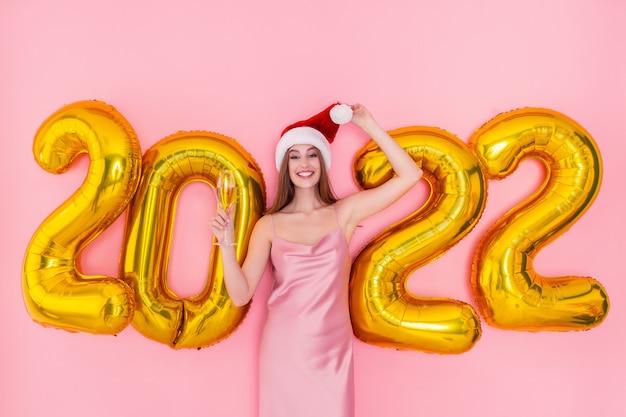 Glimlachende vrouw houdt glas champagne in kerstmuts gouden luchtballonnen nieuwjaarsconcept