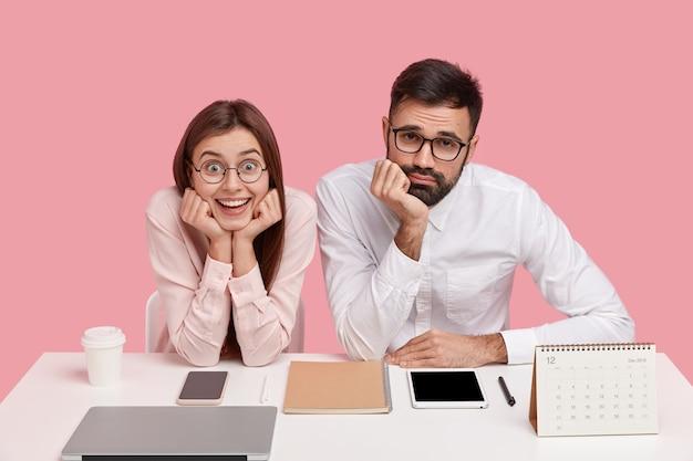 Glimlachende vrouw houdt kin met beide handen, kijkt vrolijk, draagt ronde bril, neerslachtig mannelijke collega in wit overhemd