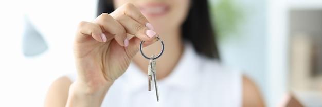 Glimlachende vrouw houdt sleutels tot huisvesting in de hand