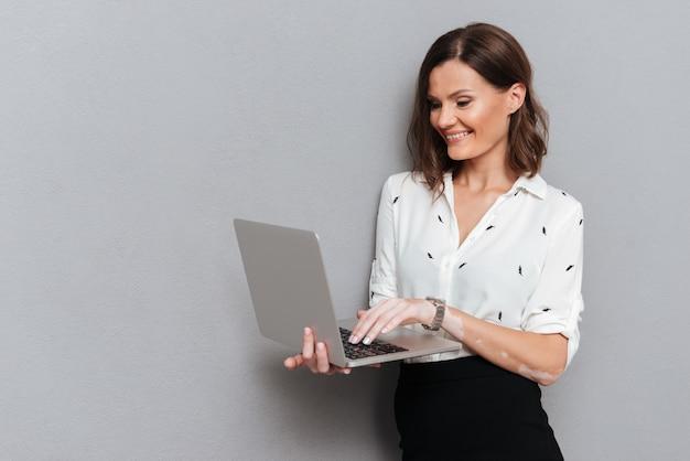 Glimlachende vrouw in bedrijfskleren die dichtbij de muur stellen en laptop computer op grijs met behulp van