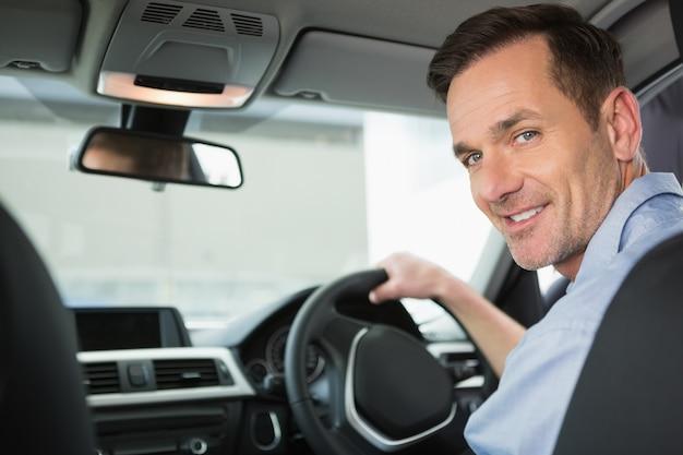 Glimlachende vrouw in de bestuurderszetel