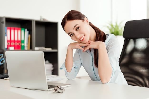 Glimlachende vrouw in de bureauzitting bij het bureau met laptop