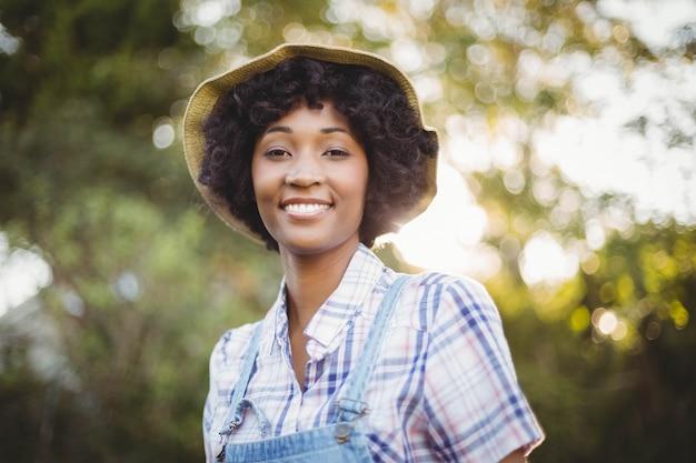 Glimlachende vrouw in de tuin die weg eruit zien