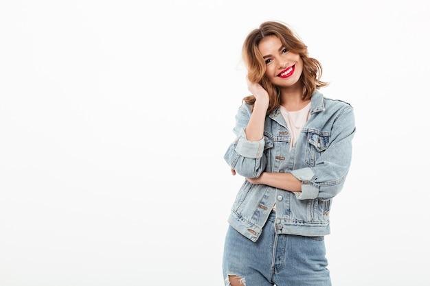 Glimlachende vrouw in denimkleren die over witte muur stellen