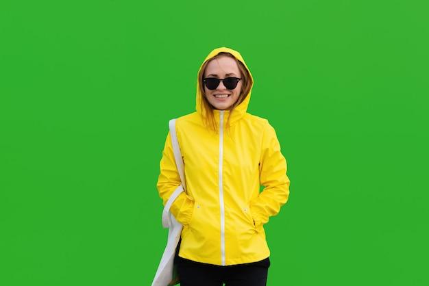 Glimlachende vrouw in een gele regenjas met zonnebril met een toteback op groene achtergrond carrying