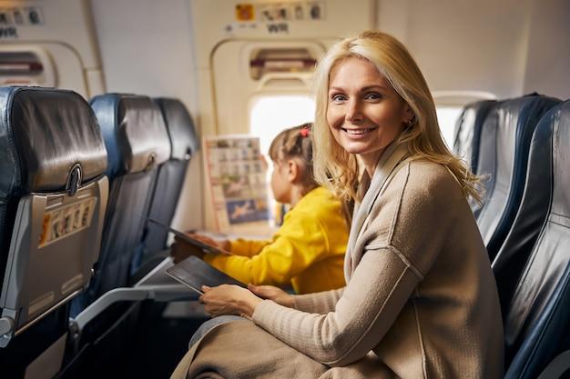 Glimlachende vrouw in een vliegtuig met een tablet
