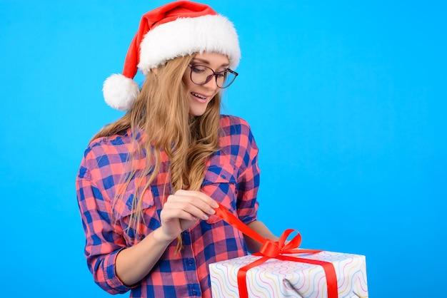 Glimlachende vrouw in geruite overhemd openingsdoos in haar handen