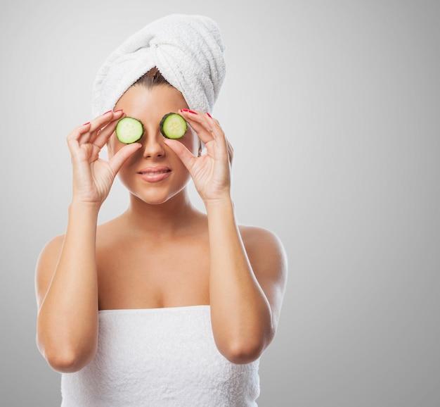 Glimlachende vrouw in handdoek met komkommer op de ogen