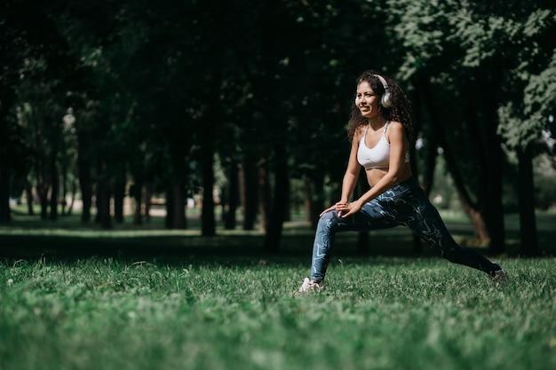 Glimlachende vrouw in hoofdtelefoons die zich uitstrekt voordat ze buiten jogt