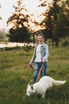 Glimlachende vrouw in jeanskleren die aan leiband witte hond op gras met vage bomen en water in avond lopen
