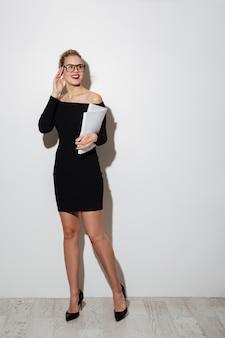 Glimlachende vrouw in jurk en bril