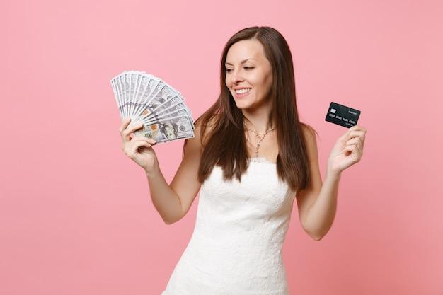 Glimlachende vrouw in kanten witte jurk met bundel veel dollars, contant geld en creditcard