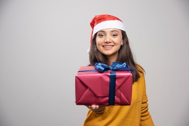 Glimlachende vrouw in kerstmanhoed die een giftdoos toont.