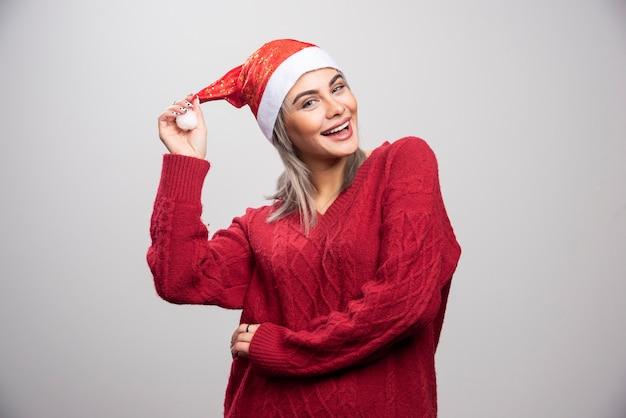 Glimlachende vrouw in kerstmuts die zich voordeed op een grijze achtergrond.