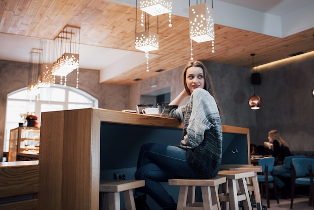 Glimlachende vrouw in koffie gebruikend mobiele telefoon en smsend in sociale netwerken, die alleen zitten