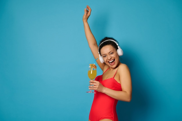 Glimlachende vrouw in koptelefoon houdt cocktail in de ene hand en steekt de andere hand op blauwe achtergrond