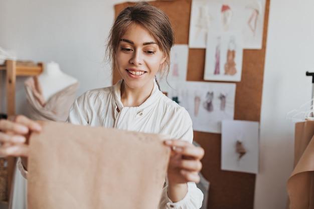 Glimlachende vrouw in lichte blouse houdt patroon vast