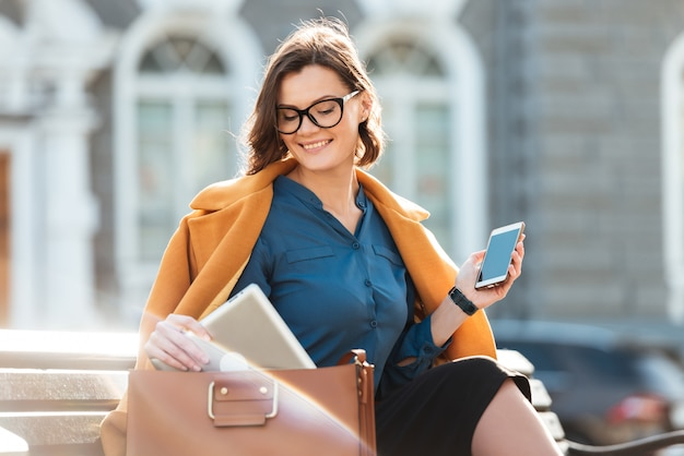 Glimlachende vrouw in oogglazen en laag die mobiele telefoon houden