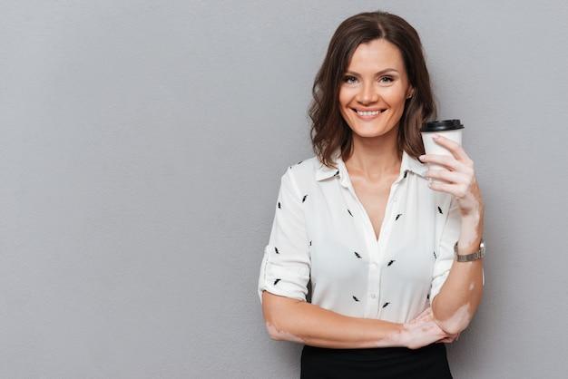 Glimlachende vrouw in overhemd het drinken koffie en het bekijken de camera op grijs