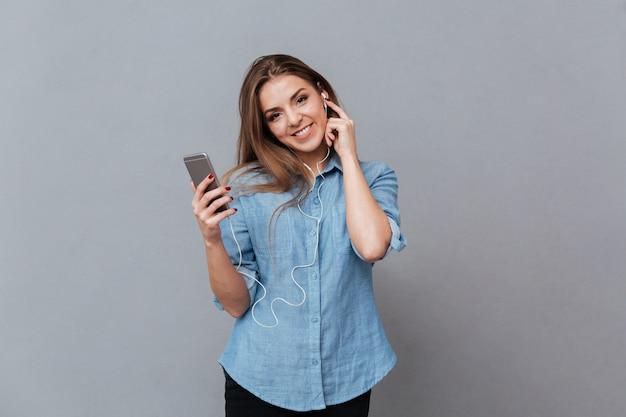 Glimlachende vrouw in overhemd het luisteren muziek op telefoon