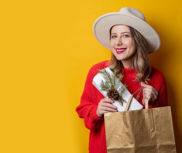 Glimlachende vrouw in rode sweater met giftdoos en het winkelen zak