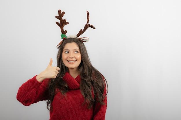 Glimlachende vrouw in rode warme trui en herten hoofdband met een duim omhoog.