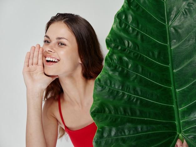 Glimlachende vrouw in rode zwembroek groene palmblad hand in de buurt van gezicht
