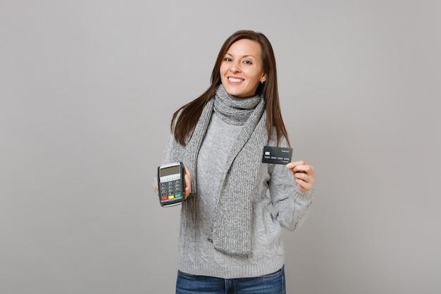 Glimlachende vrouw in sweatersjaal houdt draadloze moderne bankbetaalterminal vast om creditcardbetalingen te verwerken, geïsoleerd op een grijze achtergrond. lifestyle, oprechte emoties van mensen, concept van het koude seizoen.