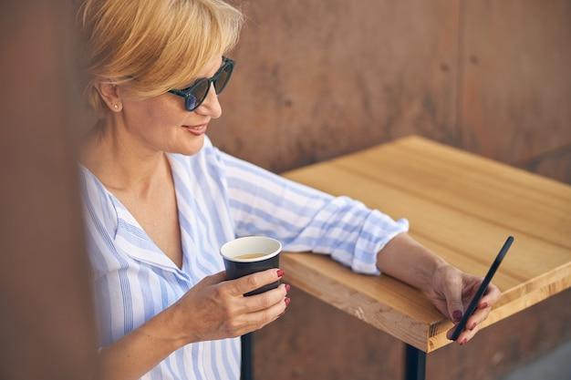 Glimlachende vrouw in trendy zonnebril met een papieren wegwerpkopje koffie in haar hand
